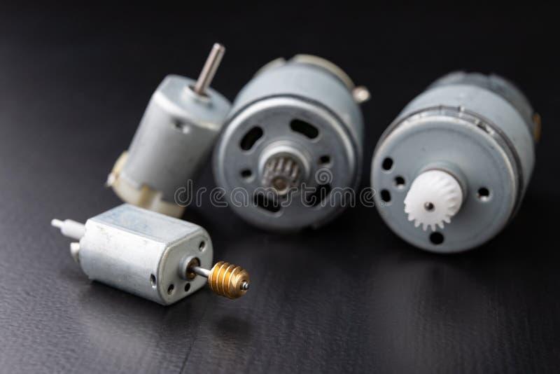 Motor elétrico pequeno em uma tabela escura de madeira Movimentação elétrica para aparelhos eletrodomésticos pequenos fotos de stock royalty free