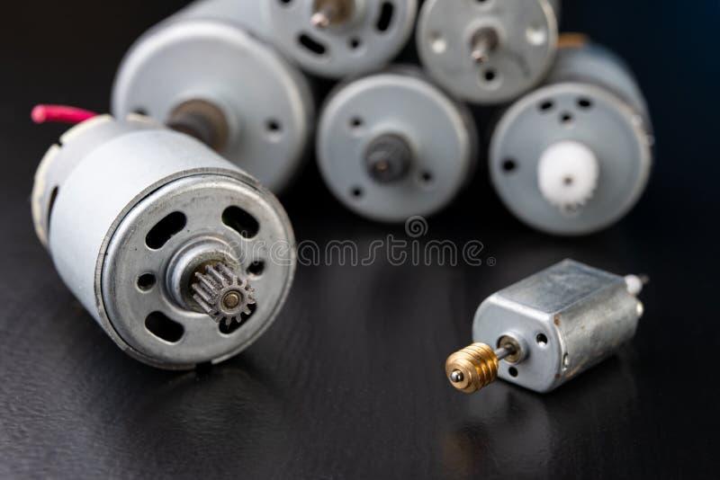 Motor elétrico pequeno em uma tabela escura de madeira Movimentação elétrica para aparelhos eletrodomésticos pequenos foto de stock