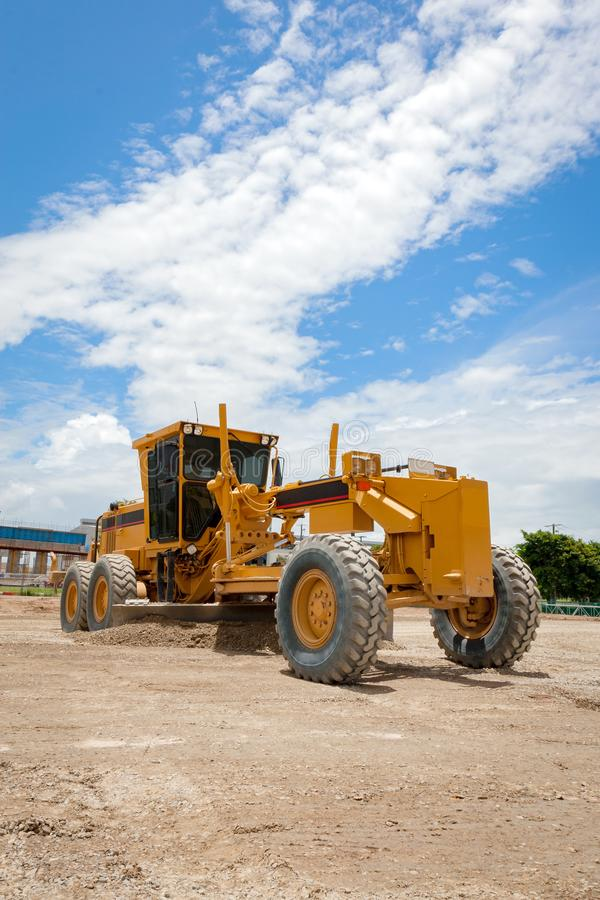 Motor Grader Civil Construction Site. Yellow Motor Grader on a Civil Construction Project Site on a sunny blue sky day stock photography