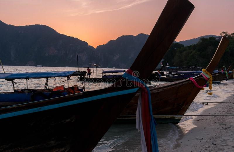 Longtail boat at sunset stock images