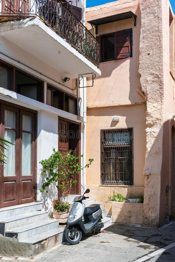 Motor scooter is staying parked near facade of old greek house in Rethymno town, Crete island, Greece.  royalty free stock image