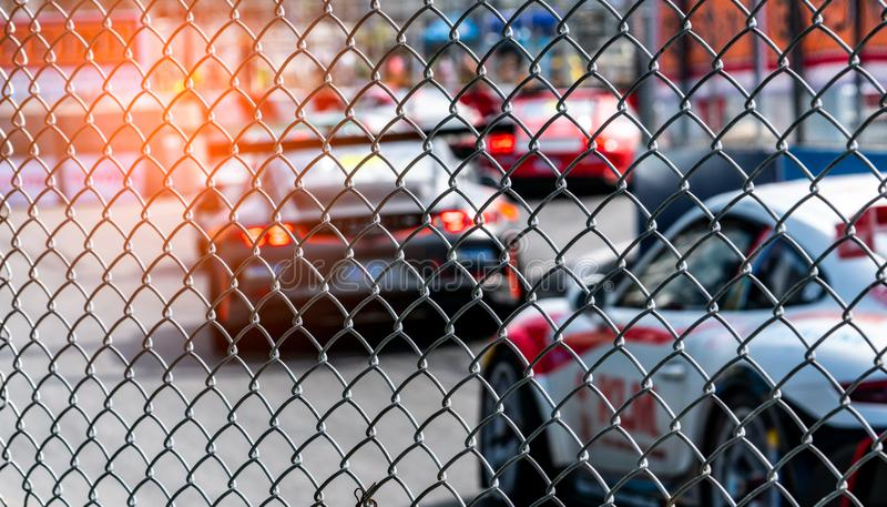 Motor sport car racing on asphalt road. View from the fence mesh netting on blurred car on racetrack background. Super racing car royalty free stock images