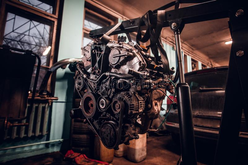 Motor van een auto op een hydraulisch hijstoestel in de workshop wordt opgeschort die royalty-vrije stock fotografie