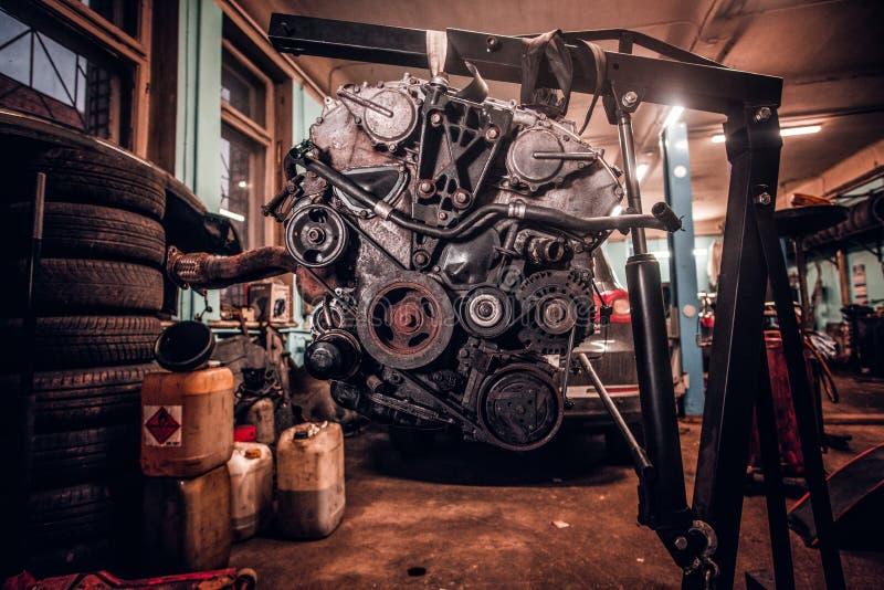 Motor van een auto op een hydraulisch hijstoestel in de workshop wordt opgeschort die royalty-vrije stock afbeelding