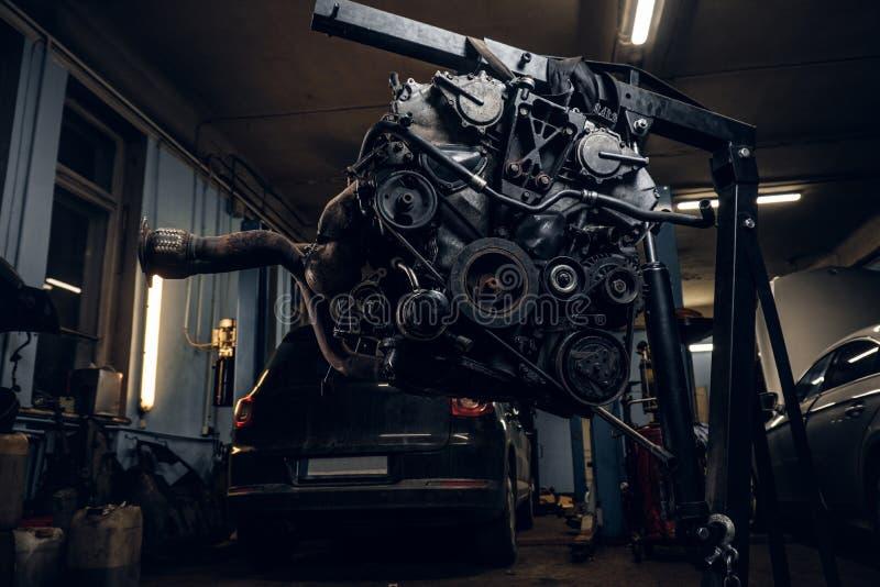 Motor van een auto op een hydraulisch hijstoestel in de workshop wordt opgeschort die stock fotografie