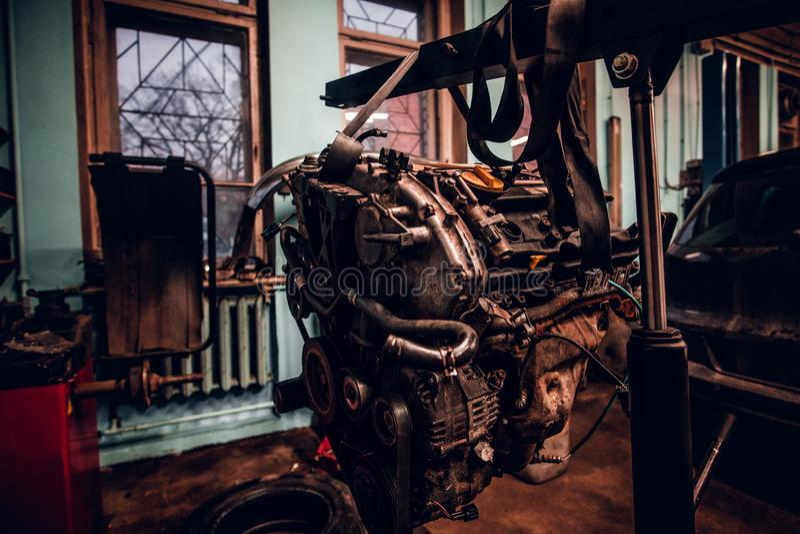 Motor van een auto op een hydraulisch hijstoestel in de workshop wordt opgeschort die royalty-vrije stock foto's