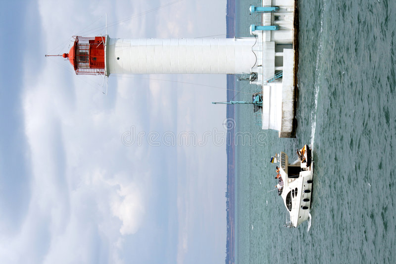 Motor yacht floats by the big beacon royalty free stock photos