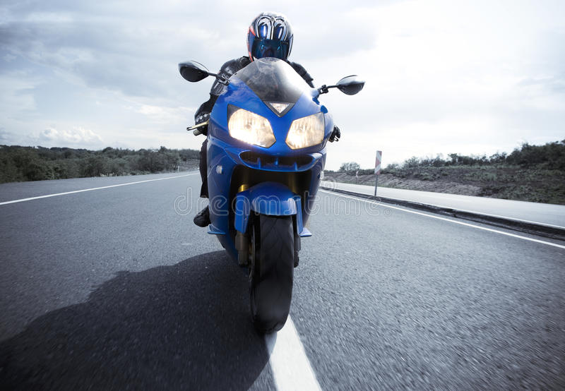 Motorbike driver on the road. Motorbike on the asphalt road with its driver royalty free stock photo