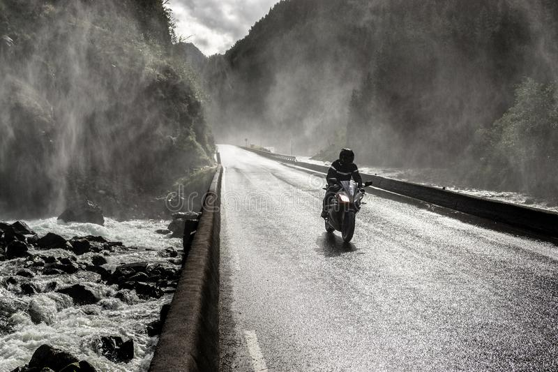 Motorbike driving fast on wet canyon valley road and bridge across river. Norway stock images