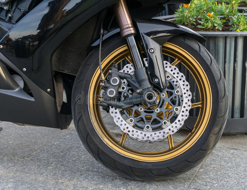 Motorbike front wheel with disc break. Detailed view of motorbike front wheel with disc break stock images