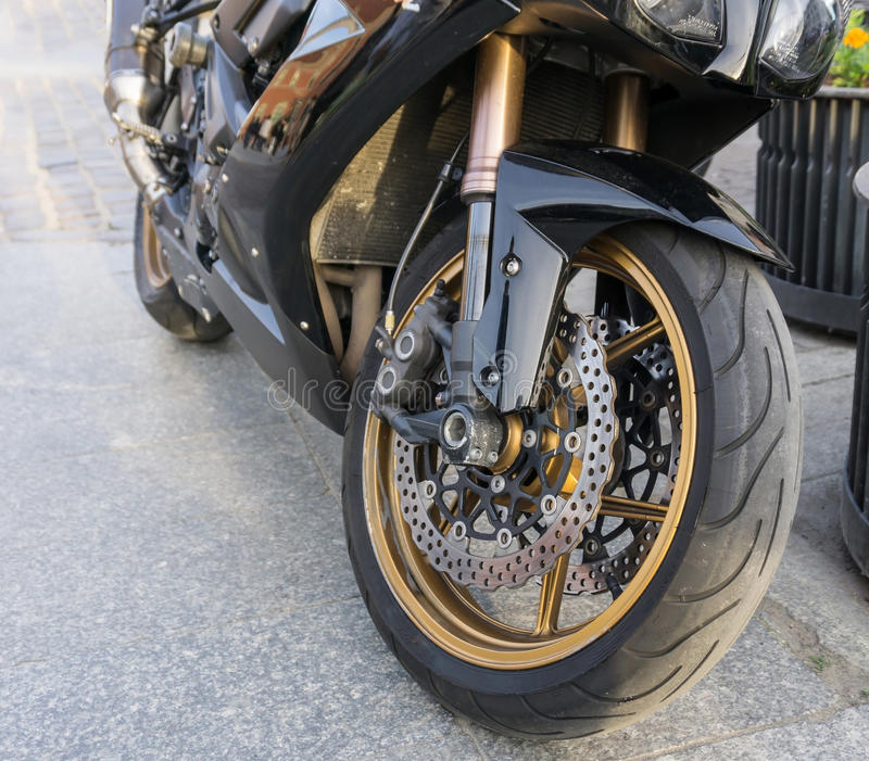 Motorbike front wheel with disc break and tire. Detailed view of motorbike front wheel with disc break and tire stock photo
