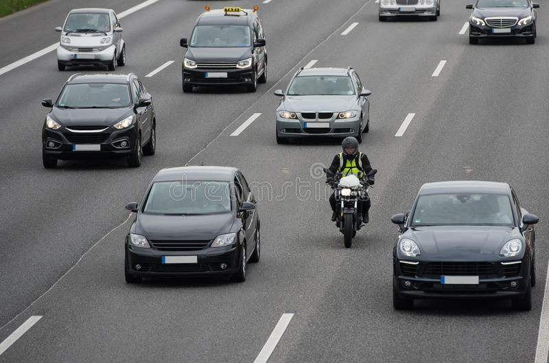 Motorbike on highway. Motorbike overtaking cars in the middle of the lanes on highway stock photography
