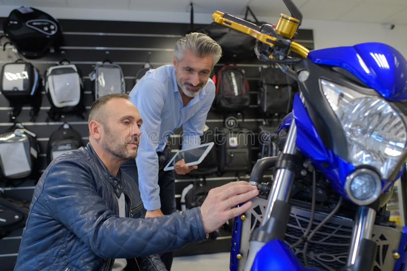 Motorbike mechanic showing issue to client stock image