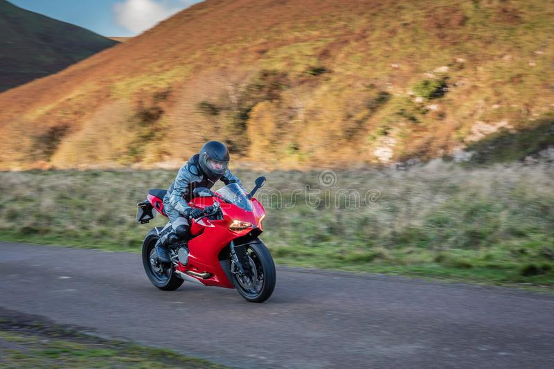 Motorbike Panning. Panning motorbike at speed to create motion blur on a country road in Upper Coquetdale, Northumberland royalty free stock images