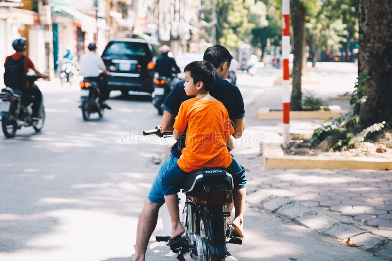 Motorbike scene of a dad and the son in Vietnam royalty free stock images