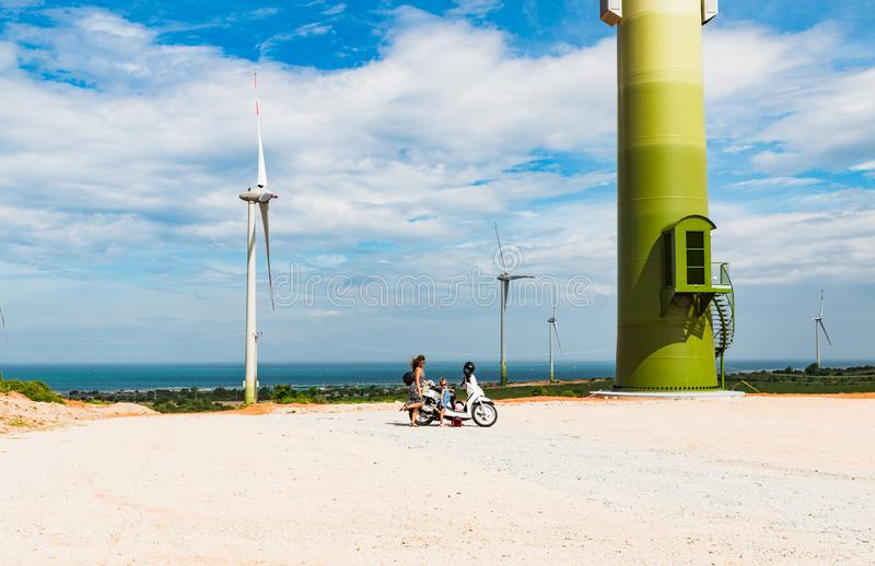 Motorbike with woman and girl stand near Wind turbine farm from clean energy near the sea. Phan Rang, Vietnam. Motorbike stand near Wind turbine farm from clean royalty free stock images