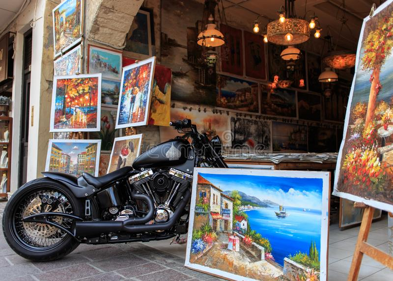 RETHYMNO, GREECE - JUNE 15 2018: Motorbike standing among the paintings on the street of the old town Rethymno stock photography