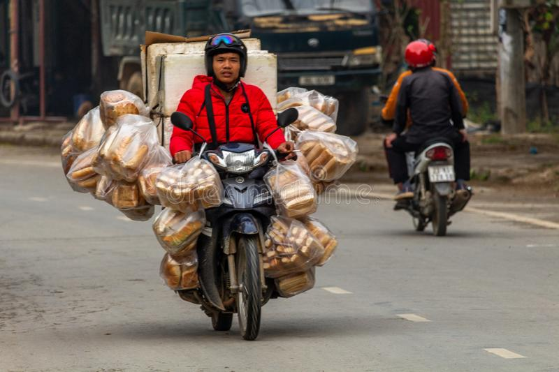 Motorbike transporting big items Vietnam. Ha Giang, Vietnam - March 17, 2018: Motorbike driver with a big load of bread on the streets of Yen Minh in northern stock photos
