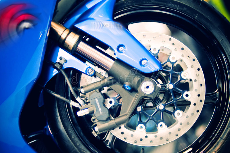 Motorbike wheel and disk brakes. Close up of a motorbike shiny wheel and disk brakes stock images