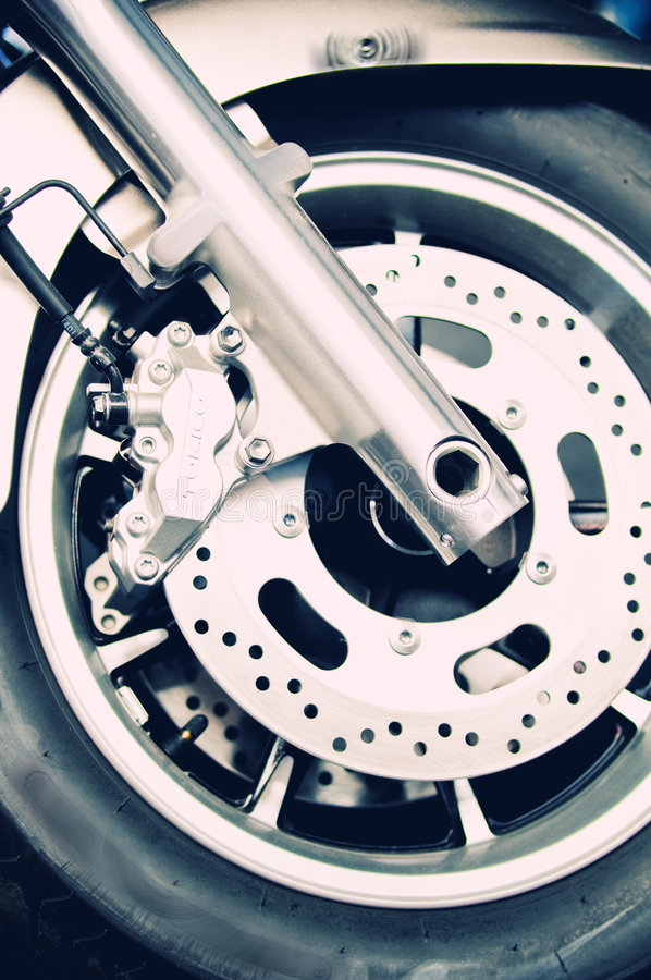Motorbike wheel and disk brakes. Close up of a motorbike shiny wheel and disk brakes royalty free stock photography