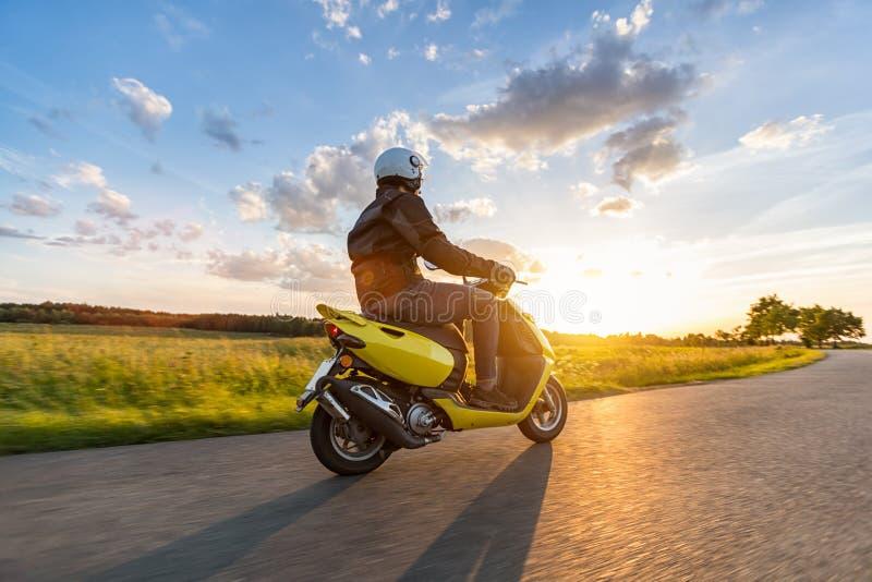 Motorbiker die op lege weg met zonsonderganghemel berijden stock foto
