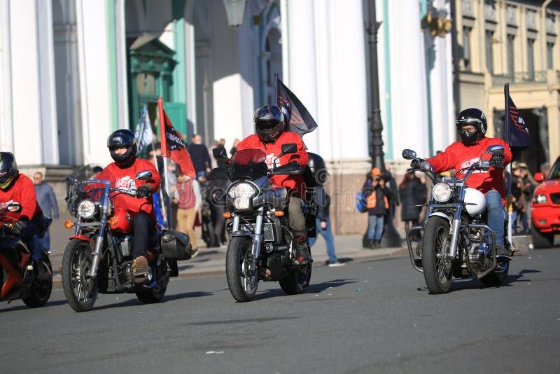 Motorbikers in magliette rosse del club sulle loro motociclette un giorno soleggiato immagini stock