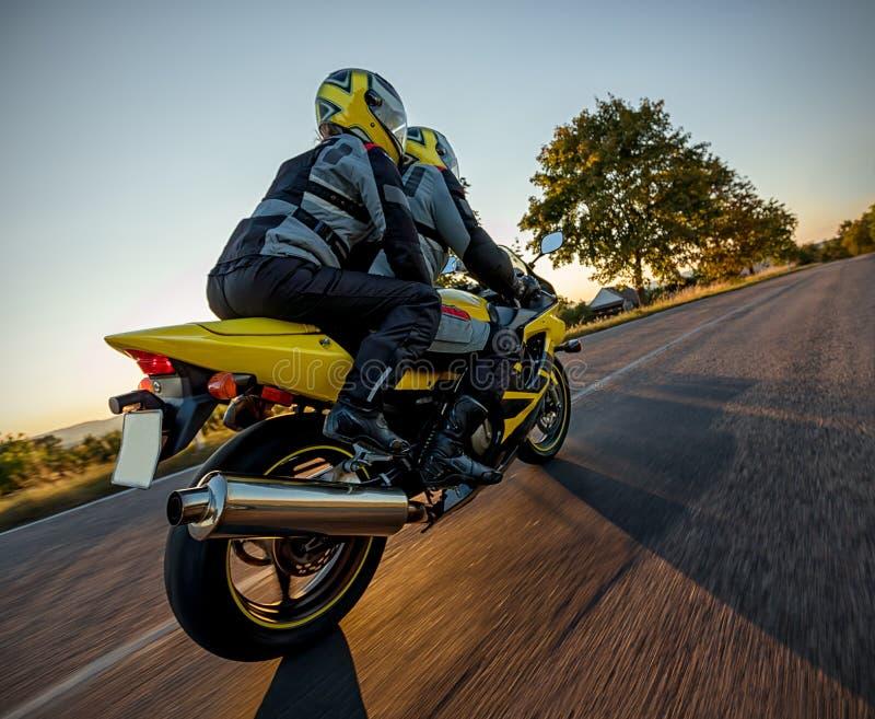 Motorbikers na equitação do velomotor dos esportes no por do sol, photog exterior fotos de stock royalty free