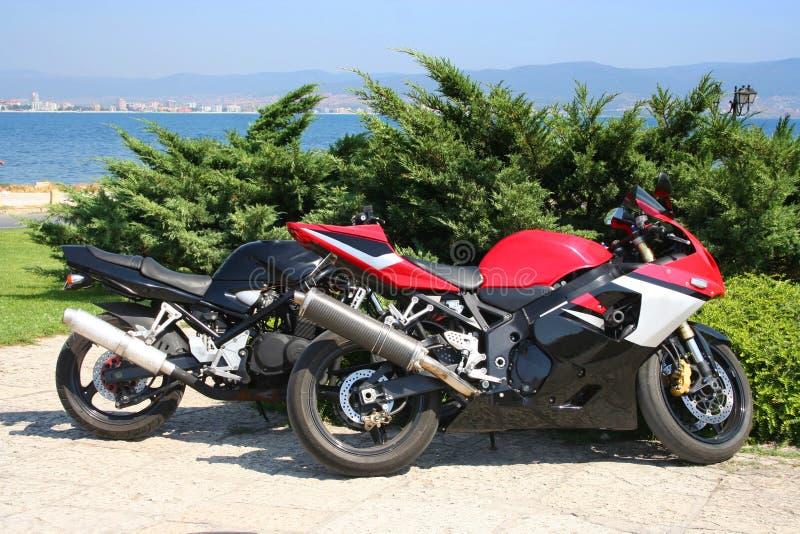 Motorbikes. Two motorbikes near the sea stock images
