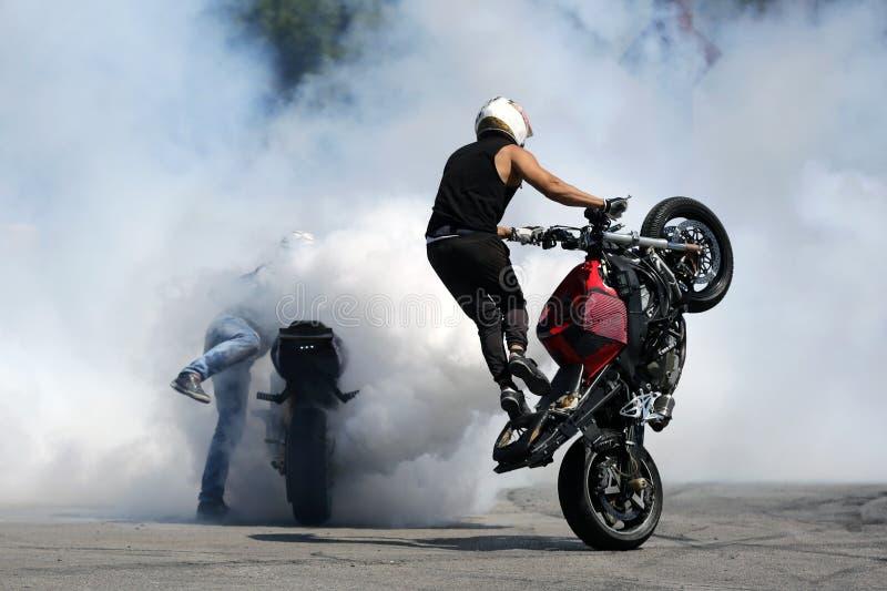 Motorbikes drift white smoke wheel. Two motorbikes burn wheels on a race track. White smoke royalty free stock photos