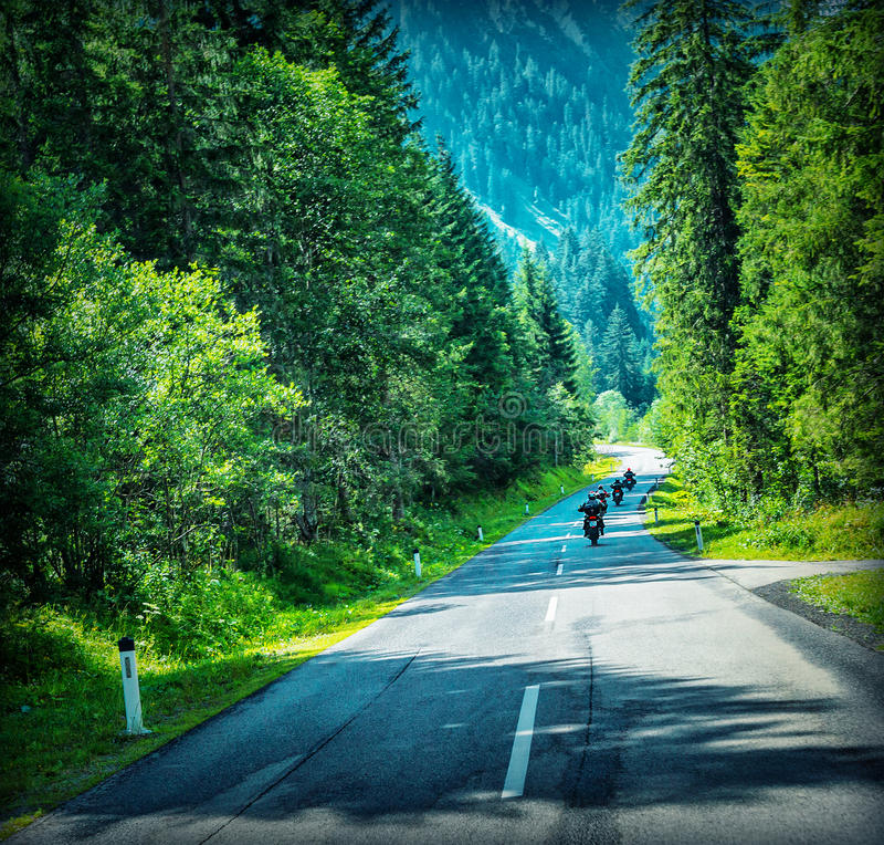 Motorbikes race. Group of sportive people travel on motorcycles in Alpine mountains, enjoying extreme sport, active lifestyle concept royalty free stock image