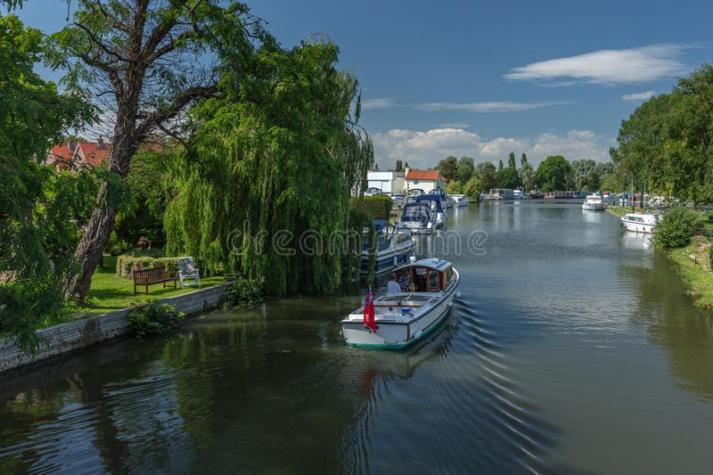 A motorboat cruises towards Beccles Quay on the River Waveney royalty free stock photos