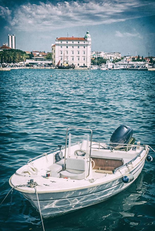Motorboat in port, Split, Croatia, analog filter. Motorboat in port, Split, Croatia. Travel destination. Summer vacation. Analog photo filter with scratches stock photography