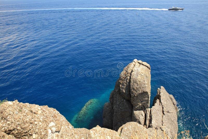 Motorboat que passa pelas rochas. imagem de stock