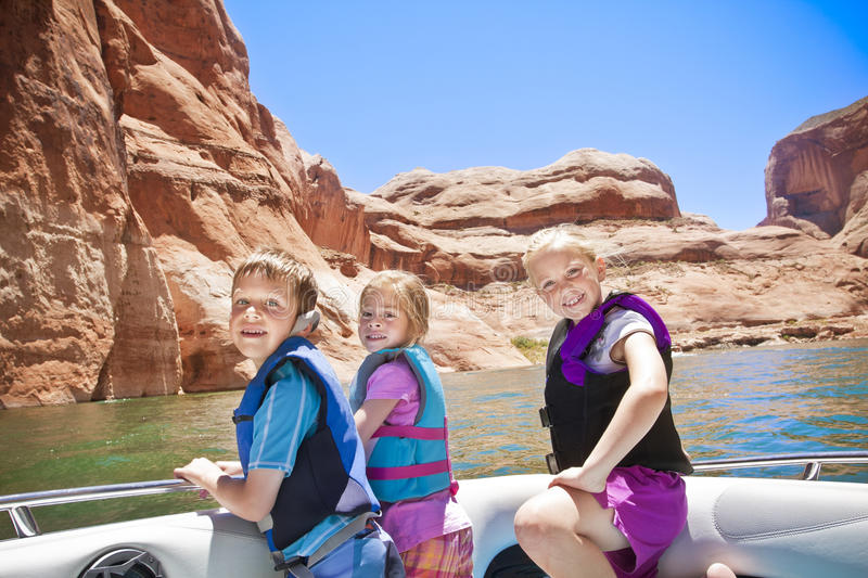 Motorboating fun - Children. Three smiling children enjoying a day on a motorboat at Lake Powell royalty free stock image