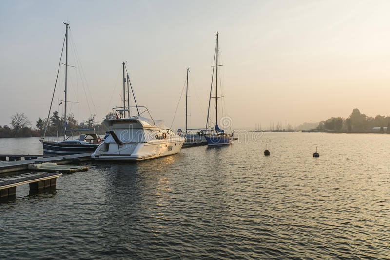 Motorboats and sailboats at the pier on the lake stock photography