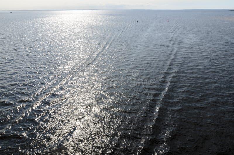 Motorboot, die bij hoge snelheid de overgaan, verliet mooie stroken op het water en hief een hoge golf op overzees met donkerblau stock afbeeldingen