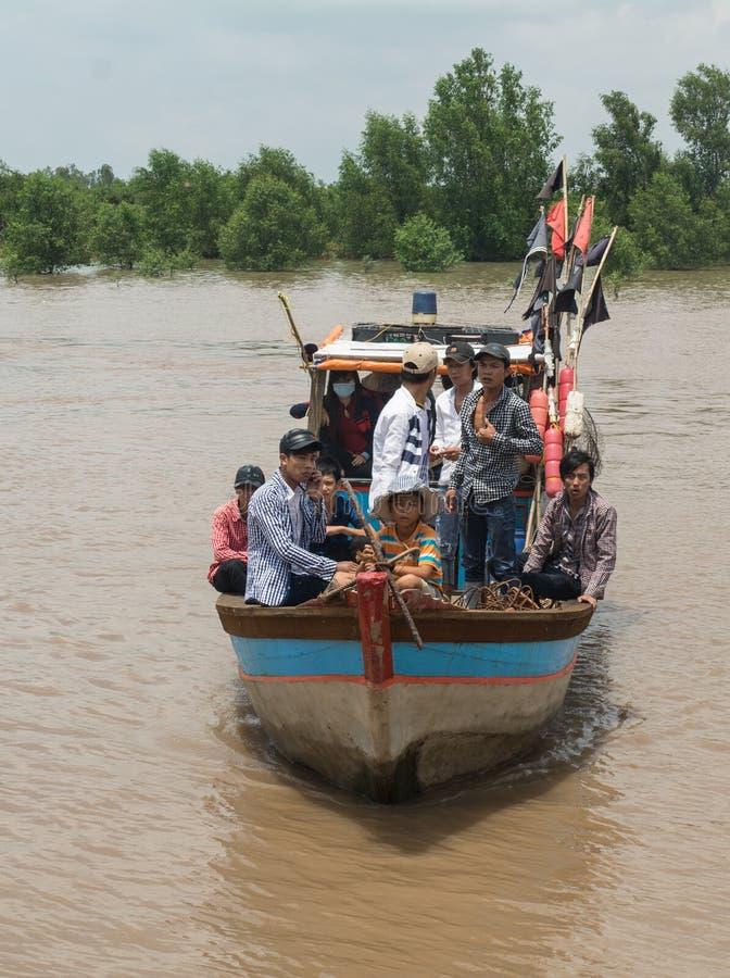 Motorboot die vele mensen op Mekong rivier vervoeren stock foto