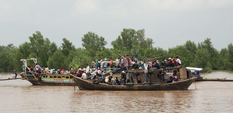 Motorboot die vele mensen op Mekong rivier vervoeren stock afbeelding