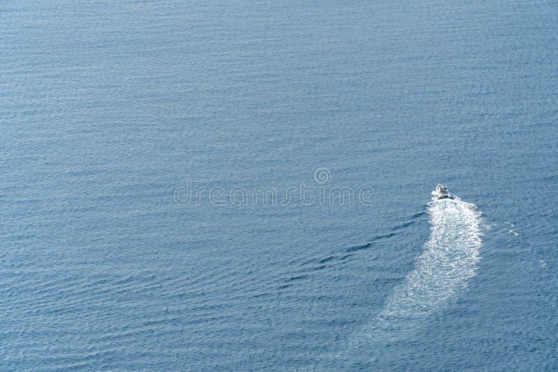 Motorboot in heldere blauwe overzees bij een groot afstandsconcept actieve recreatie, vakantie door het overzees, het vermaak en  stock foto's