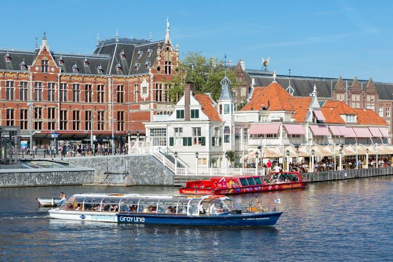 Motorboot met toeristen in Amsterdam voor de centrale post stock fotografie
