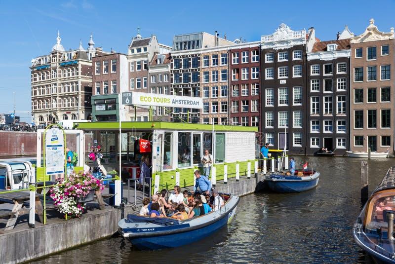Motorboot met toeristen op een vertrekplaats van het kanaalcruises van Amsterdam stock foto