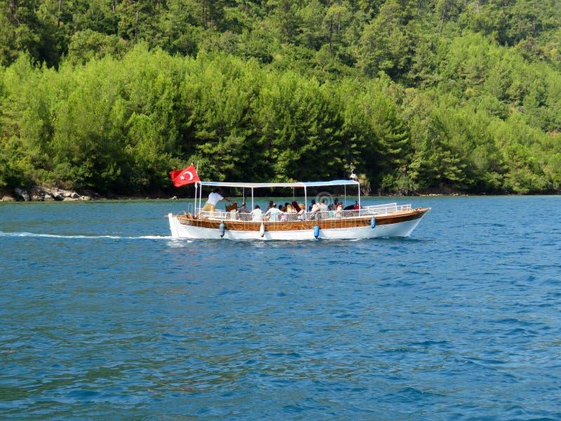 Motorboot mit Passagieren nahe dem bewaldeten Seeufer stockfotografie