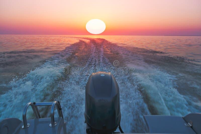 Motorboot op het overzees in zonsondergangtijd stock afbeeldingen