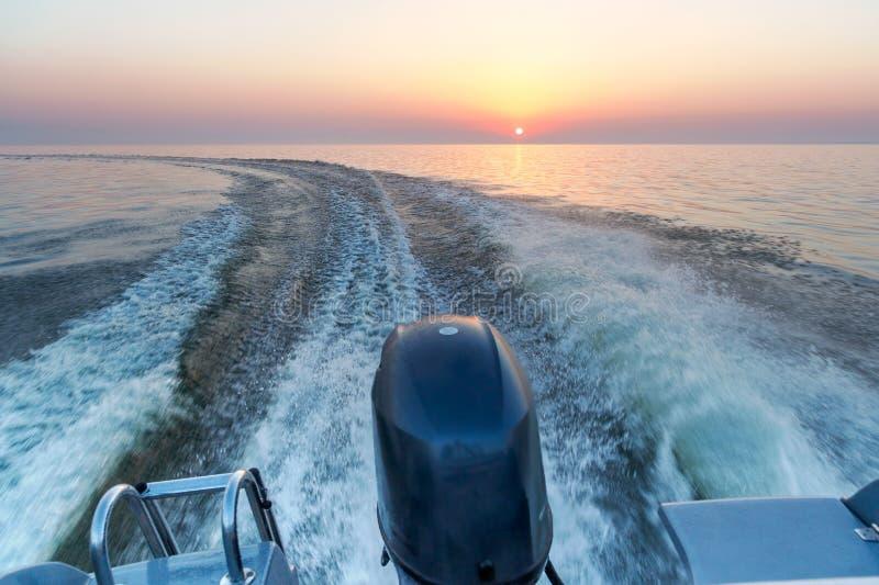 Motorboot op het overzees in zonsondergangtijd stock foto's