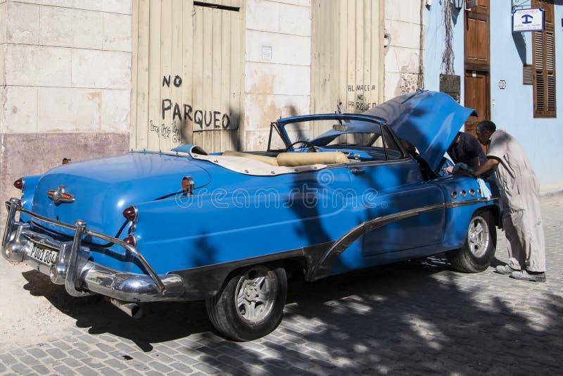 Mechanics try to repair classical car in street of Havana stock images