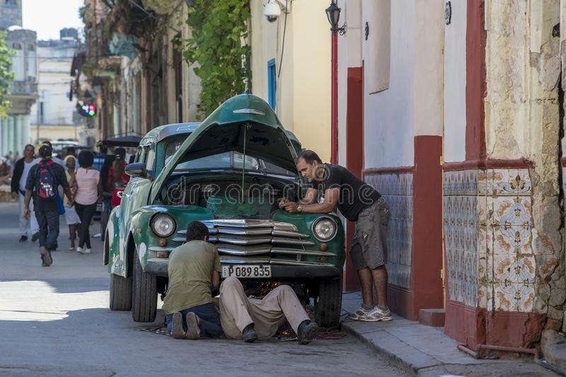 Mechanics try to repair classical car in street of Havana stock photography
