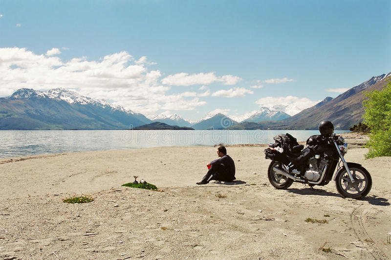 Motorcyce rider on lakeside. A motorcyclist and his bike on a coffee break on the shore of a lake, New Zealand royalty free stock photos