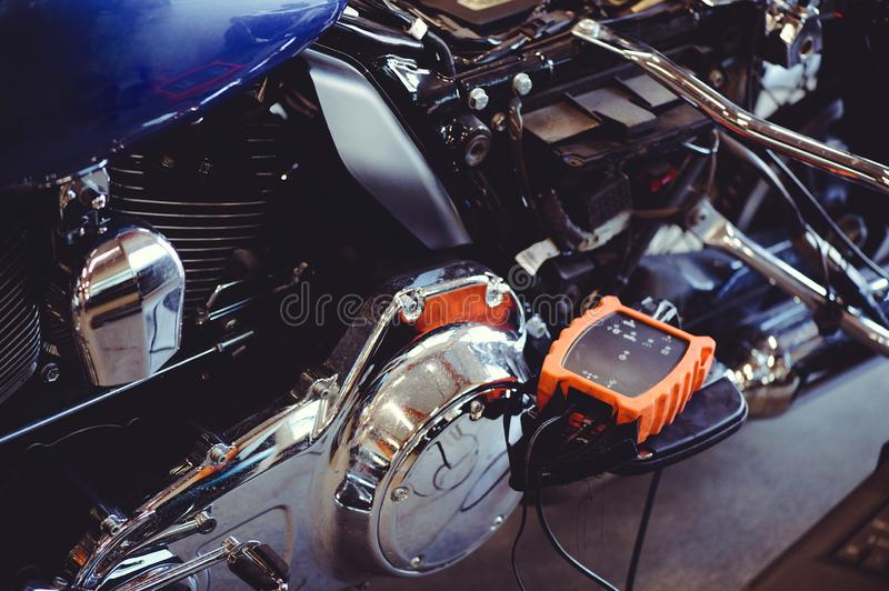 Motorcycle adjustment device. repair and programming of a motorcycle. The device is connected to workshop tools, a modern garage,. Storage and repair. This bike royalty free stock image