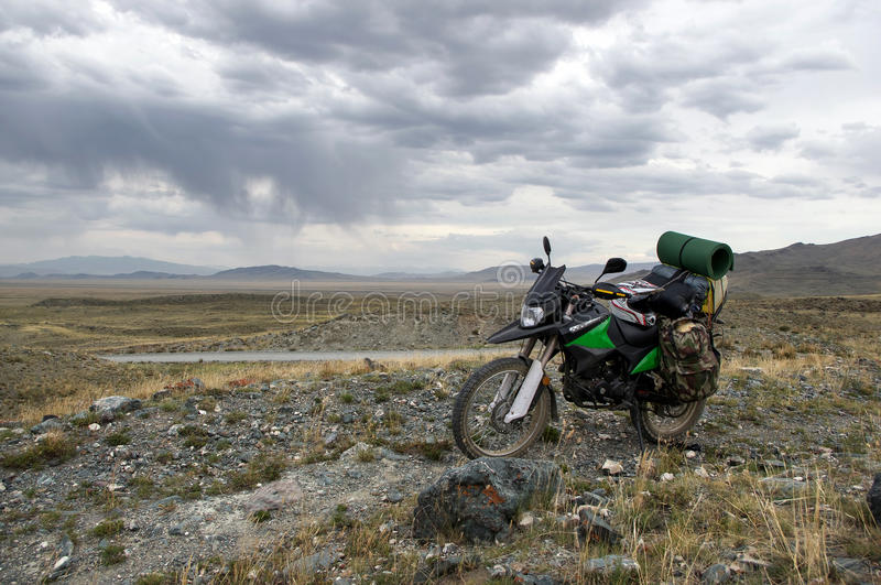 Motorcycle alone enduro traveler with suitcases standing on rocky plateau in cloudy weather. On the background of endless steppe and dark gloom fog mountain royalty free stock photos