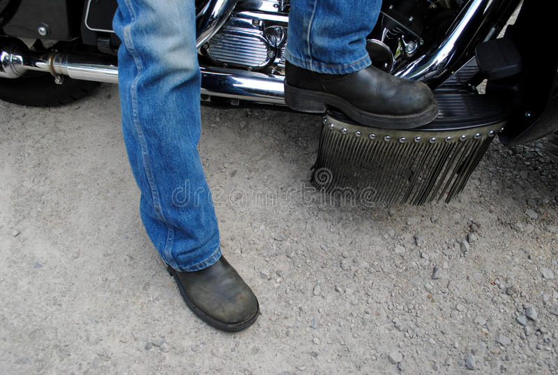 Motorcycle Boots. Men's feet in motorcycle boots, on a bike stock photography